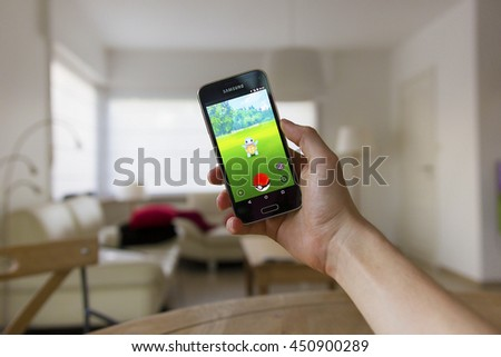 LENDELEDE, BELGIUM-JULY 11TH 2016:a hand holding a Samsung Galaxy S5 mini mobile phone which displays the Pokemon Go app on the touch screen.An unaltered illustrative editorial image in a living room. - stock photo