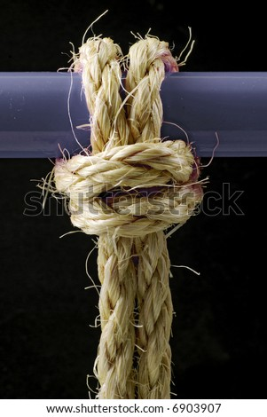 length of coarse rope tied to bar with cow hitch knot - stock photo