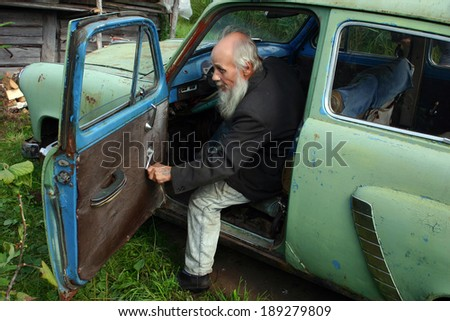 LENINGRADSKAYA AREA SAINT-PETERSBURG, RUSSIA - AUGUST 23, 2006: Valentin Stepanovich Shramko born in 1938, Elderly man sits in an old Soviet-made car, Moskvich 403, , green.