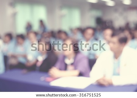 Lens blur on crowd sitting in convention seminar room - stock photo