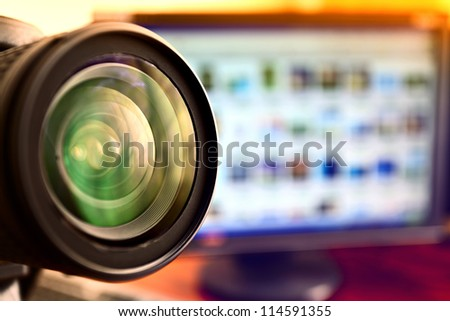 lens of camera and computer monitor - stock photo