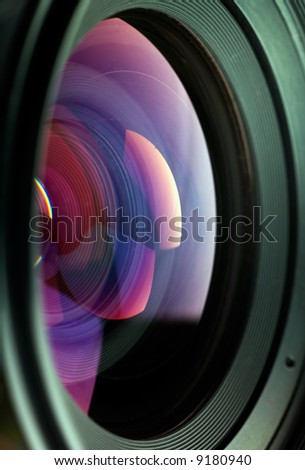 Lens, with refracted light and rainbow colors caused by refraction and the lens coating.  Shallow DOF.