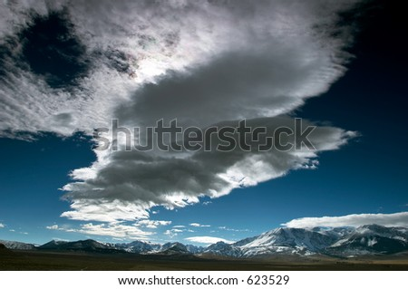 Lenticular clouds on the blue sky with distant mountains in the background, California - stock photo