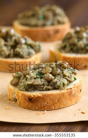 Lentil and parsley spread on bread slices served on paper, photographed with natural light (Selective Focus, Focus in the middle of the first canape) - stock photo