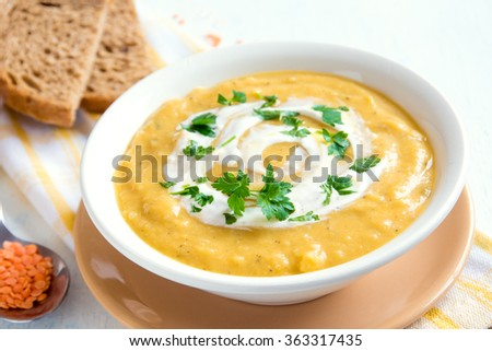 Lentil and pea cream soup with cream cheese and parsley in bowl over rustic wooden background - stock photo