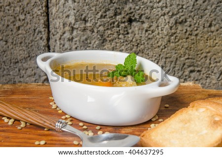 Lentil soup with peppermint decorated, rustic background.