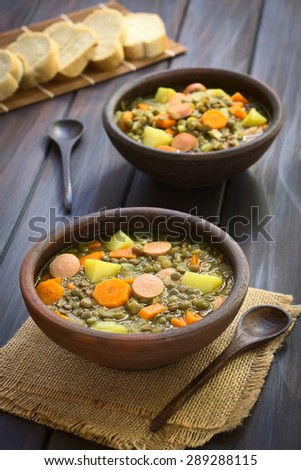 Lentil soup with potato, carrot, onion, sausage slices, with slices of baguette bread in the back, photographed on dark wood with natural light (Selective Focus, Focus on the middle of the first soup) - stock photo