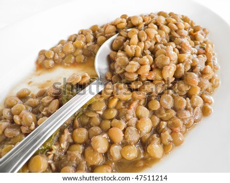 Lentil soup with spoon on white dish. - stock photo