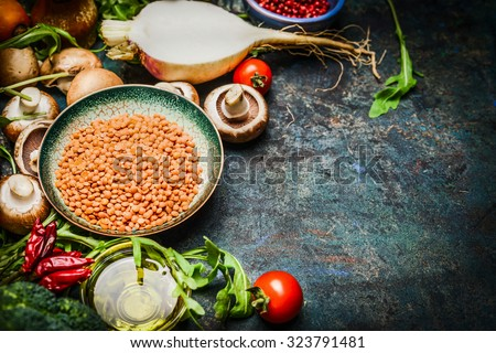 Lentil with fresh vegetables and ingredients for cooking on blue rustic background, close up. Vegan food , vegetarian , diet or  healthily cooking concept. - stock photo