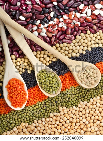 lentils, beans, peas, soybeans, legumes with spoons, textured background - stock photo