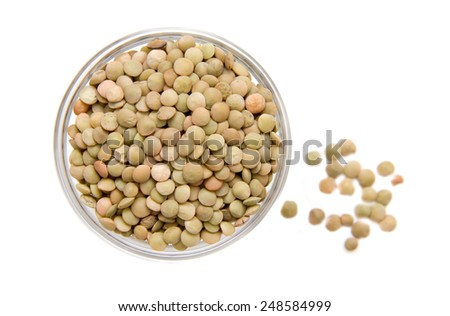 Lentils in glass bowl on white background viewed from above - stock photo