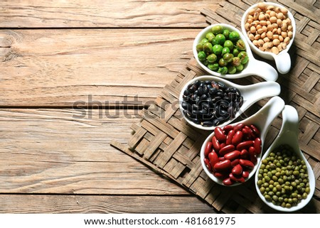 lentils in spoon on wooden background. mung bean, soybean, red bean , black bean