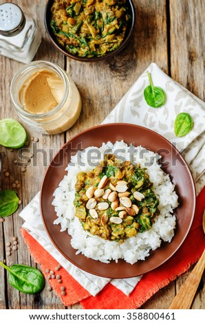 lentils, peanut butter spinach curry with rice on a dark wood background. toning. selective Focus - stock photo