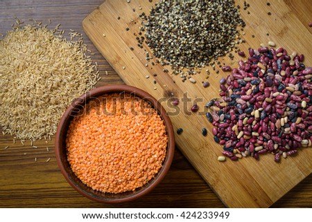 Lentils, red beans and brown rice on a wooden table and board - stock photo
