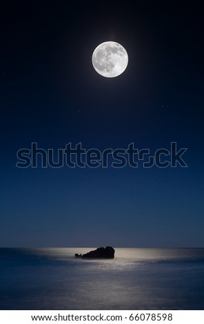Leo Carillo Beach just outside of Malibu.  The moon shines over a rock in the ocean, reflecting in the water - stock photo