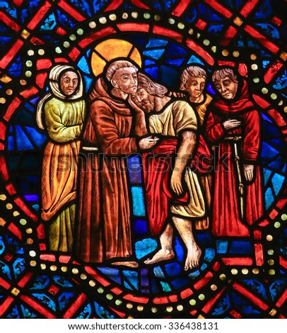 LEON, SPAIN - AUGUST 12, 2014: Stained Glass window depicting a Christian Saint hugging Christ in the Cathedral of Leon in Castile and Leon, Spain. - stock photo