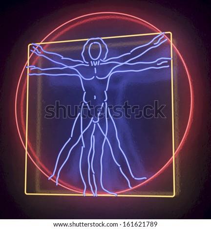 Leonardo Da Vinci's Vitruvian Man in blue, red and yellow Neon Tube Finish, Homo Quadratus, 3d rendering on black background - stock photo