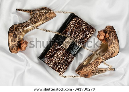 Leopard bag and shoes  lying on white  fabric, can use as background
