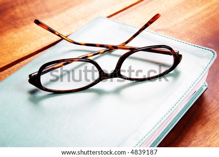 Leopard patern reading glasses lying on a book. Everything is lying on a wood table - stock photo