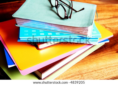 Leopard patern reading glasses lying on a pile of books and files.Everything is lying on a wood table - stock photo