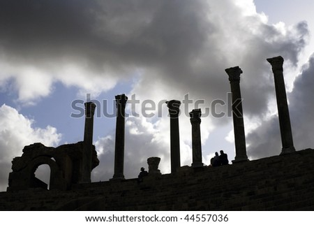 Leptis Magna, Libya. Corinthian columns in silhouette at the Amphitheater with dramatic gloomy sky.