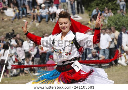"LEPUSHE, ALBANIA - AUGUST, 11: a competitor to ""Miss Mountain"" is performing in a traditional dance and she wearing a traditional Albanian dress. Shot in 2012 in Lepushe, village of commune Kelmend - stock photo"
