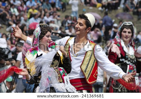 "LEPUSHE, ALBANIA - AUGUST 11: a young couple in albanian costume performs a courtship dance. The beautiful girl is the winner of ""Miss Mountain 2012"" in Lepushe, commune of Kelmend. Shot in 2012 - stock photo"
