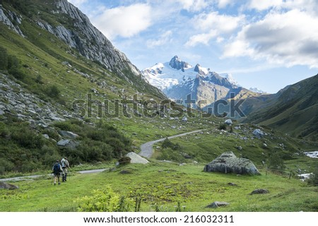 LES CHAPIEUX, FRANCE - AUGUST 27: Hikers walking with Glacier Needles in the background. The region is a stage at the Mont Blanc tour, which crosses three countries. August 27, 2014 in Les Chapieux. - stock photo