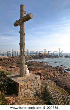 LES SABLES D'OLONNE, FRANCE: A religious Cross facing the wild coast with the jetty and the lighthouse in the background