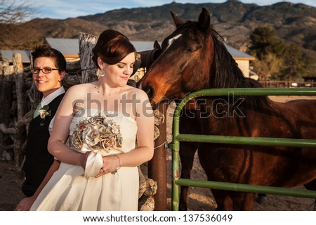 Lesbian bride with eyes closed with horse touching her back - stock photo