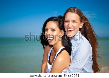 Lesbian couple at the beach laughing - stock photo