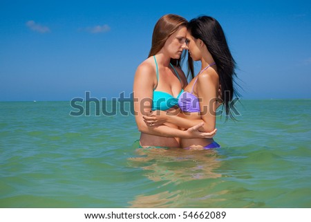 Lesbian couple on vacation, standing in water - stock photo