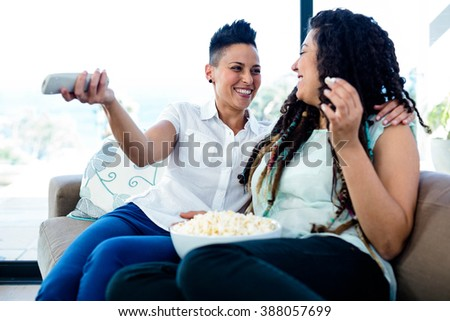 Lesbian couple taking and smiling while watching television - stock photo