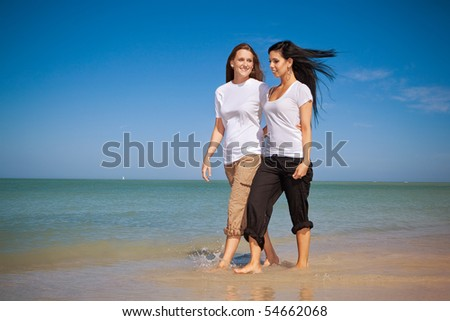 Lesbian couple walking on a beach on vacation.