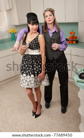 Lesbian couple with drinks and cigar in kitchen - stock photo