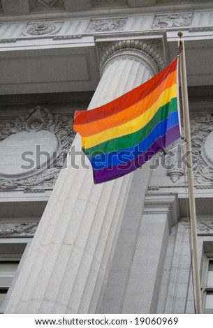 Lesbian, gay, bisexual, and transgender pride flag flying outside a government building - stock photo