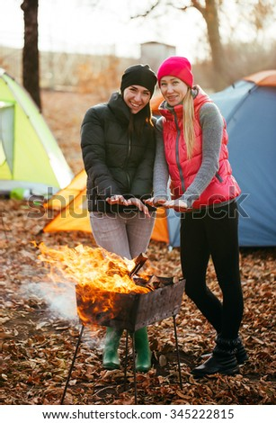 lesbian girls are heated by the fire. - stock photo