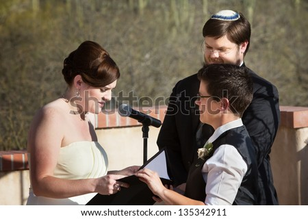 Lesbian white couple reciting marriage vows in ceremony - stock photo