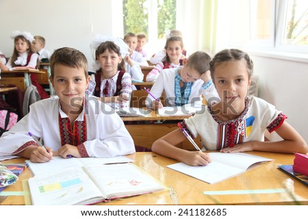 Lesson in Ukrainian schools. Children write in a notebook - stock photo
