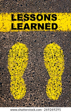 Lessons Learned  message. Conceptual image with yellow paint footsteps on the road in front of horizontal line over asphalt stone background. - stock photo