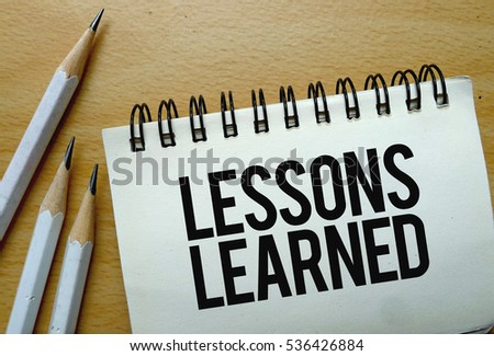 Lessons Learned text written on a notebook with pencils