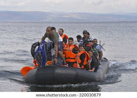 LESVOS, GREECE  SEPTEMBER 24, 2015: Refugees arriving in Greece by  boat from Turkey.  These Syrian refugees land their boat near Molyvos, Lesvos. Turkey can be seen in the background. - stock photo