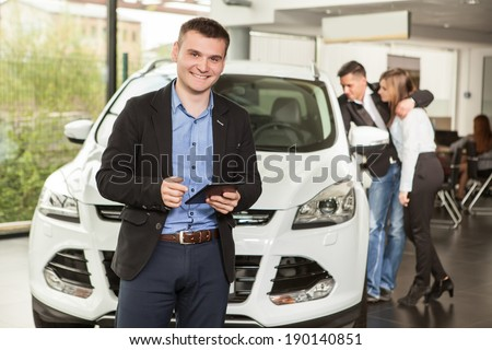 Let me assist you in your vehicle search. Handsome young classic  salesman standing at the dealership with the customers on the background - stock photo