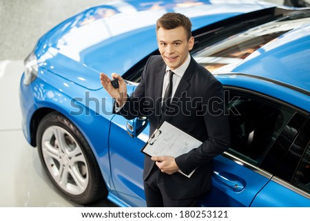 Let me assist you in your vehicle search. Top view of handsome young classic car salesman standing at the dealership holding a key - stock photo