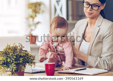 Let me examine your working place! Little baby girl looking away while crawling on her mothers place of work - stock photo