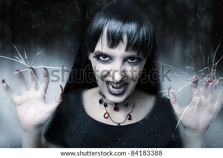 let me in. Horror and halloween concept. Female vampire looking out at rainy, cracks and misted window glass at the night