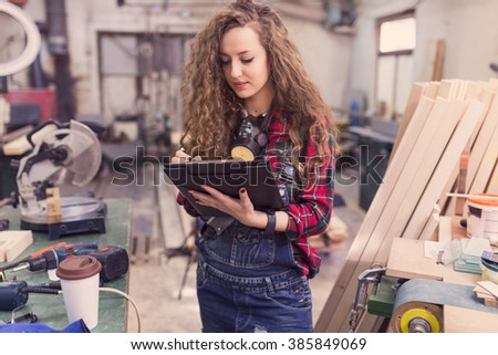 Let me just check my to do list for today. Woman carpenter standing in her workshop . Selective focus, depth of field, focus on notebook - stock photo