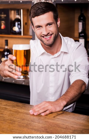 Let me quench your thirst! Handsome young male bartender in white shirt stretching out glass with beer and smiling while standing at the bar counter - stock photo