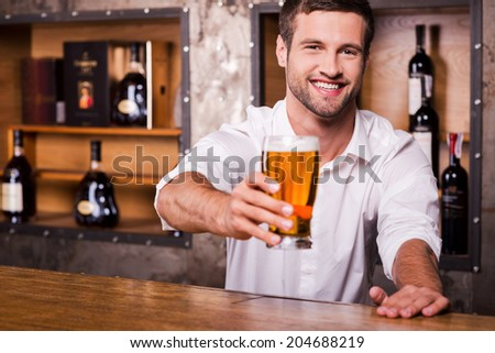 Let me quench your thirst! Happy young male bartender in white shirt stretching out glass with beer and smiling while standing at the bar counter