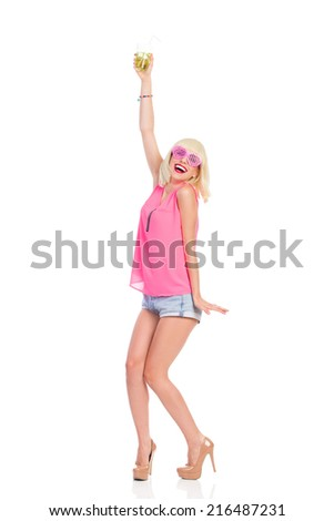 Let's dance and drink! Shouting blonde young woman in high heels, pink top and jeans shorts raising hand with lime drink. Full length studio shot isolated on white. - stock photo